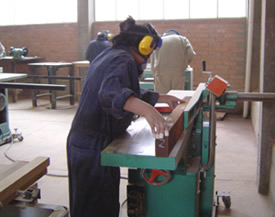 Adriana working on the jointer, creating wooden puzzles in Bolivia.
