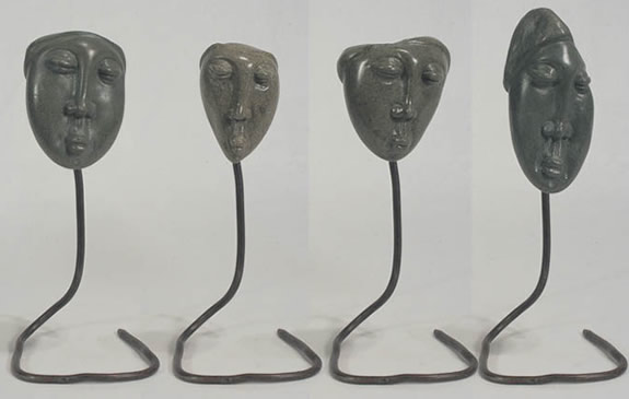 Soapstone faces on metal stands from haiti.